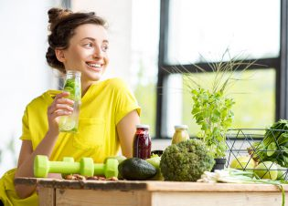 Portrait of a young sports woman in yellow t-shirt sitting indoors with healthy food and dumbbells on the table